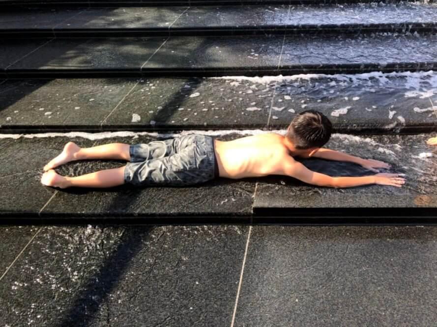 カスケードの水遊び場で寝そべる子供